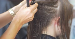 Stock Video Footage of Stylist Hairdresser is Separating a Hair Strands Fixing them with Barrette