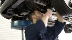 Handsome mechanic reparing a car Stock Footage