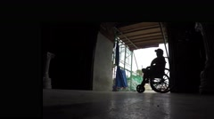 Wheelchair beggar at church portal ruins. Silhouettes Arkistovideo