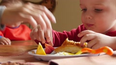 Children eating their lunch at table in kitchen Stock Footage