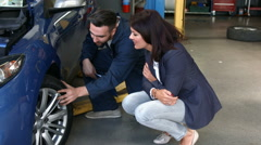 Mechanic talking to a female customer Arkistovideo