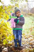 Children playing with autumn fallen leaves in park Stock Photos