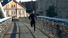 Young man jogging on the bridge in the city, super slow motion Stock Footage