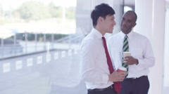 4K 2 Businessmen in conversation in modern glass office building. - stock footage
