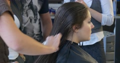 Stock Video Footage of Stylist Hairdresser is Combing Hairs Making a Fire Cut For a Woman with Long