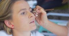 Stock Video Footage of Woman Stylist Beautician is Applying an Eyes Makeup Eyeliner For a Model Young