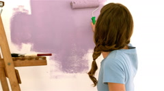 Pretty girl redecorating a wall with brush Stock Footage
