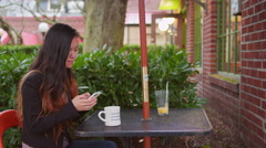 A young woman uses her phone until her date sits back down at the table Stock Footage