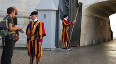 Chief of guard of Papal Swiss guard explains  road the got lost tourists Stock Footage