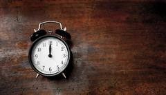 Classic alarm clock noon time on wood Stock Photos