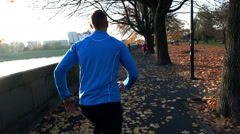 Man jogging in the autumn park, super slow motion Stock Footage