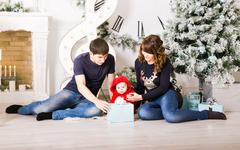 Christmas Family with baby opening gifts. Happy Smiling Parents and Child at Stock Photos