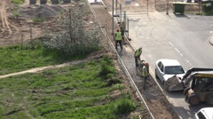Tractor unload rubble and workers team level it on pavement place. 4K Stock Footage