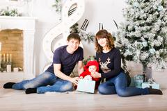 Christmas Family with baby opening gifts. Happy Smiling Parents and Child at - stock photo