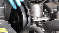 Car mechanic removing camshaft pulley and timing belt Stock Footage