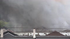 Burning warehouse buildings with black smoke rising from roof. 4K Stock Footage
