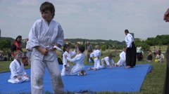 Young children with martial master train aikido skills in public park. 4K Stock Footage