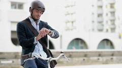 Man riding bicycle on city street using tablet and smart watch Stock Footage