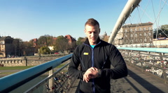 Young man with smartwatch jogging on the bridge in the city, slow motion Stock Footage