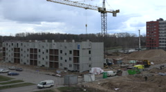 Stock Video Footage of builders with crane attach concrete block house wall part. 4K