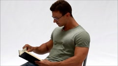 Young man reading book laughing - stock footage