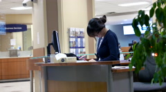 One side of receptionist dealing of customer data inside Royal bank. Stock Footage