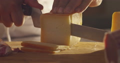 Stock Video Footage of Super slow motion macro of a middle aged chef cutting cheese with knife