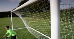 Young goalkeeper stopping a ball during a soccer match. Shot on RED Epic. Stock Footage