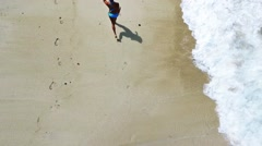 Aerial view of young woman with a slender figure is running at beach Stock Footage