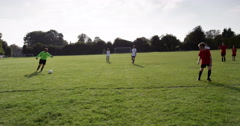 A sporty young boy kicking football towards the goal and scoring a goal. Arkistovideo