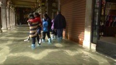 Sea level rise - Venice high tide floods shops, family - steadicam - stock footage