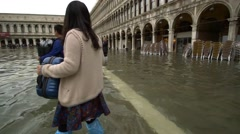 Sea level rise - Venice tourists carry luggage at high tide 2 - stock footage