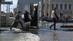 Sea level rise - Venice tourists go ashore through sea water waves - stock footage