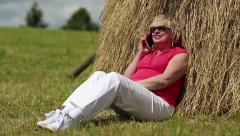 Woman sits near haystack and communicates via mobile phone Stock Footage