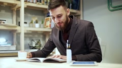 beadrded man is reading magazine with e-cigarette vape in cafe - stock footage