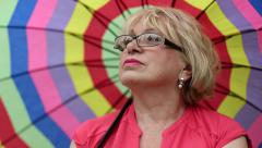 Senior woman in glasses with colorful umbrella Stock Footage