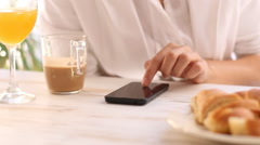 Woman using smartphone at a breakfast morning Stock Footage