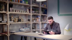 Casual businessman reading on tablet pc at the cafe and smoking e-cigarette vape Stock Footage