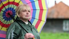 Senior woman with colorful umbrella Stock Footage