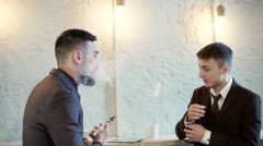 Two smiling business men smoking e-cigarette in cafe Stock Footage