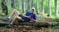 Man with red smartphone lies on a fallen tree in the forest HD Footage