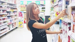 Beautiful caucasian young woman in supermarket choosing some healthy food - stock footage