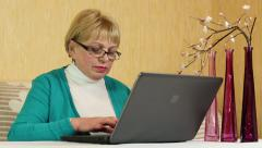 Senior woman types text uses laptop. Woman with notebook Stock Footage