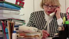 Senior woman chief accountant in glasses talks on telephone - stock footage