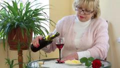 Woman sits at a table and drinks red wine Stock Footage