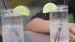 Two glasses of water with limes on a cafe table - stock footage