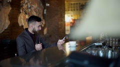 Modern hipster businessman drinking coffee in cafeand working on tablet smoking Stock Footage