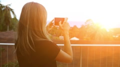 Stock Video Footage of Tourist taking photograph of sunset in Thailand on island. Young woman with long