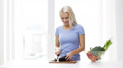 Stock Video Footage of smiling young woman chopping eggplant at home