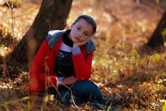 The sad girl sits on an autumn grass. - stock photo